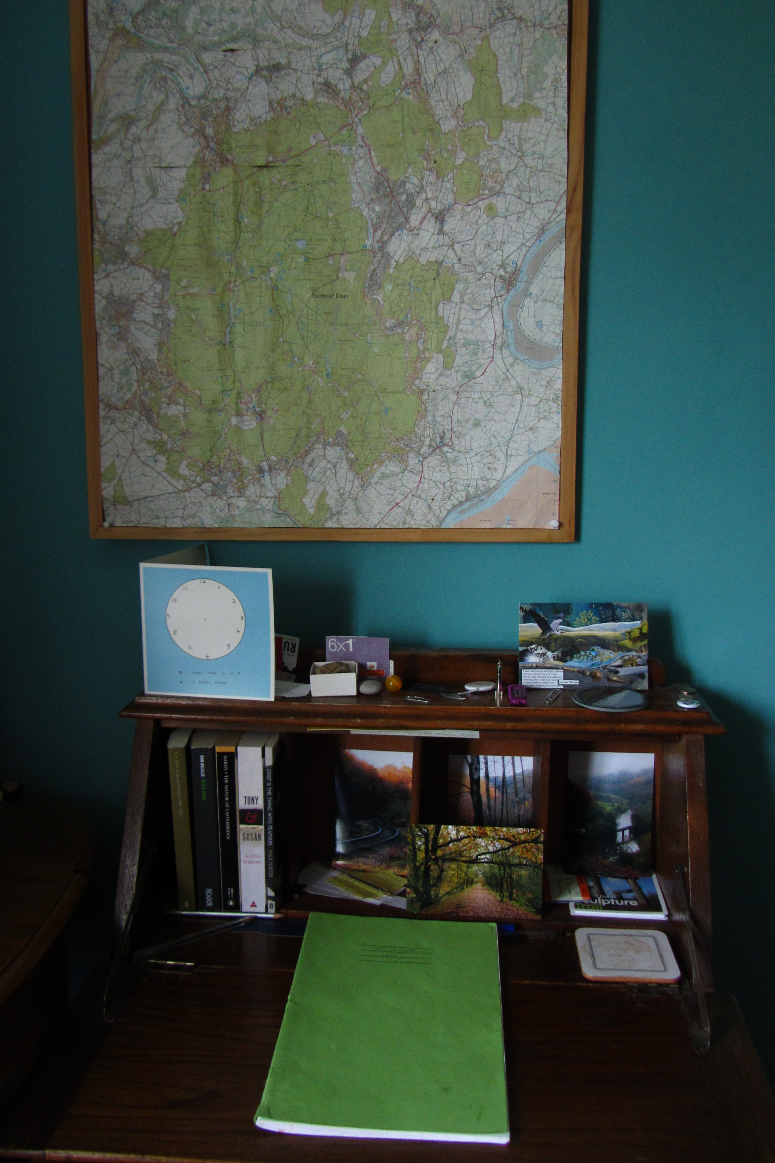 Writing desk. Blue wall with a map of the Forest of Dean. On the desk are the books TS Eliot Collect Poems, White Noise by Don DeLillo, The Mayor of Casterbridge by Thomas Hardy, Tony and Susan by Austin Wright, and Grief is the Thing with Feathers by Max Porter. Also photographs of the Forest of Dean in Autumn, a book of 6 first class stamps, and in the centre of the desk is a green notebook.